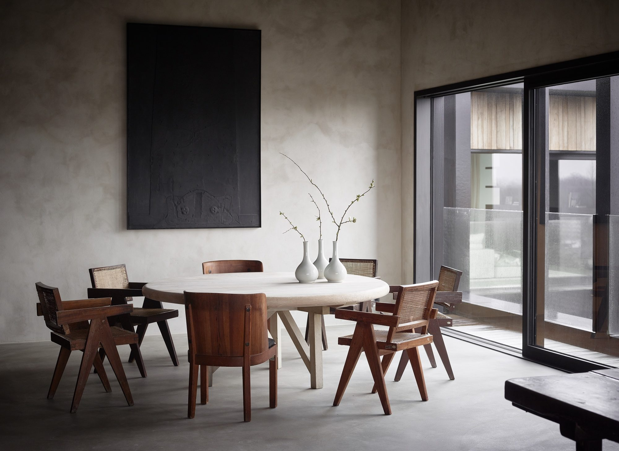 Round dining table designed by axel vervoordt with white korean porcelain and 1950s cane office chairs by pierre jeanneret